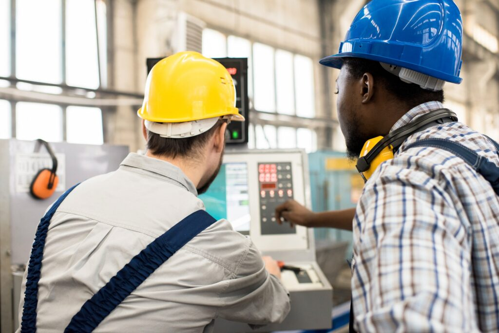 Busy workers discussing program of factory automated machine
