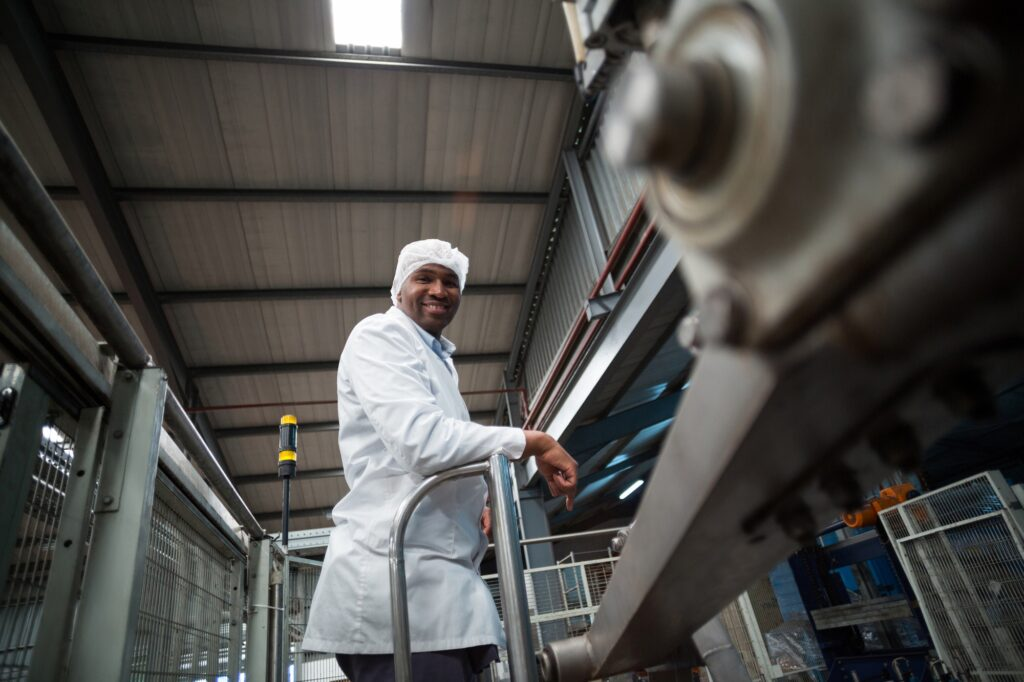 Smiling factory engineer standing in bottle factory